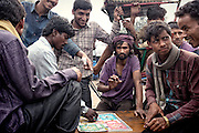 Group of men playing a game in the streets of Old Delhi, India.