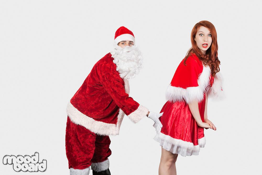 Portrait of Santa touching Mrs. Santa inappropriately against gray background