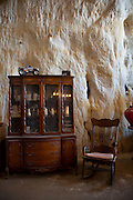 Festus, Missouri: An antique armoire and rocking chair seem incongurous next to the cave walls of Curt and Deborah Sleeper's 2,000 square foot home. It is is built inside a 17,000 square foot cave in this small town south of St. Louis. (Photo: Ann Summa).