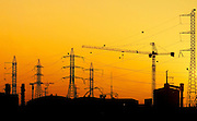 Israel, Negev, Lachish region, Construction crane and high power lines at sunset