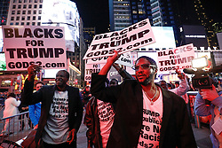"© Licensed to London News Pictures. 09/11/2016. New York City, USA. A group of men holding signs reading ""BLACKS FOR TRUMP"", react to news that Donald Trump looks likely to be elected as the next president of the United States, while gathering in Times Square, New York City, on Wednesday, 9 November. Photo credit: Tolga Akmen/LNP"