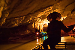Asia, Vietnam, Son Ha, Thien Ha Galaxy Grotto cave. Tour guide rowing boat.