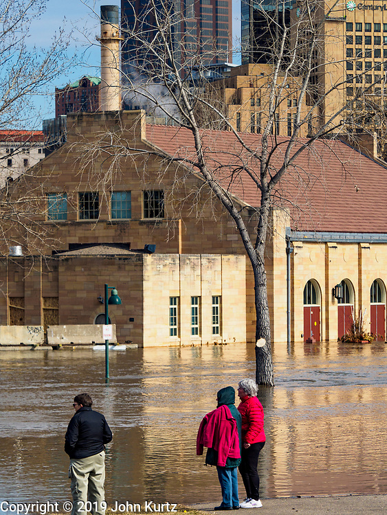 29 MARCH 2019 - ST. PAUL, MN: People look at a flooded building on Harriet Island in St. Paul. The Mississippi River through the Twin Cities has already hit flood stage. Several roads and parks in St Paul are already closed in anticipation of higher flood levels. Weather forecasters and hydrologists have backed off a little on earlier predictions of severe flooding because the snow melt has been slower than expected.      PHOTO BY JACK KURTZ