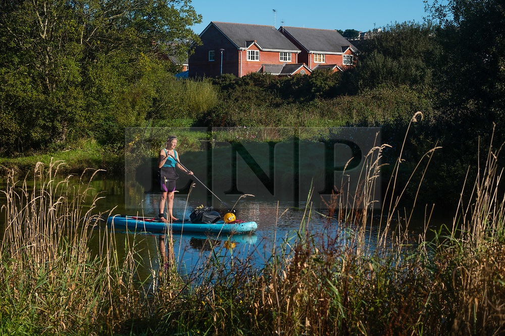 © Licensed to London News Pictures. 27/09/2018/. Aberystwyth, UK. Environmental campaigner GILLY THOMAS out on her paddleboard, voluntarily patrolling the River Rheidol in Aberystwyth, looking out for and collecting pplastic rubbish, on a sunny and warm 'Indian summer' morning in Aberystwyth , as the UK heads into a period of settled warm sunny weather. Photo credit: Keith Morris/LNP