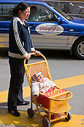 Woman with baby in traditional baby carriage, Shanghai street. China has a one child policy to reduce population.