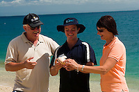 A Coral Princess guide shows tourists a local sea shell on Pelorus Island, the Great Barrier Reef, far north Queensland, Australia.