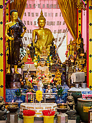 "24 JUNE 2017 - BANG KRUAI, NONTHABURI: An altar used in ""resurrection"" or rebirthing ceremonies at Wat Ta Kien (also spelled Wat Tahkian), a Buddhist temple in the suburbs of Bangkok. People go to the temple to participate in a ""Resurrection Ceremony."" Thai Buddhists believe that connecting people by strings around their heads, which are connected to a web of strings suspended from the ceiling, amplifies the power of the prayer. Groups of people meet and pray with the temple's Buddhist monks. Then they lie in coffins, the monks pull a pink sheet over them, symbolizing their ritualistic death. The sheet is then pulled back, and people sit up in the coffin, symbolizing their ritualist rebirth. The ceremony is supposed to expunge bad karma and bad luck from a person's life and also get people used to the idea of the inevitability of death. Most times, one person lays in one coffin, but there is family sized coffin that can accommodate up to six people. The temple has been doing the resurrection ceremonies for about nine years.     PHOTO BY JACK KURTZ"