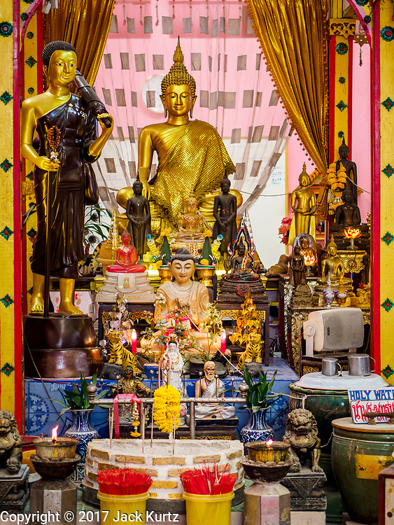 """24 JUNE 2017 - BANG KRUAI, NONTHABURI: An altar used in """"resurrection"""" or rebirthing ceremonies at Wat Ta Kien (also spelled Wat Tahkian), a Buddhist temple in the suburbs of Bangkok. People go to the temple to participate in a """"Resurrection Ceremony."""" Thai Buddhists believe that connecting people by strings around their heads, which are connected to a web of strings suspended from the ceiling, amplifies the power of the prayer. Groups of people meet and pray with the temple's Buddhist monks. Then they lie in coffins, the monks pull a pink sheet over them, symbolizing their ritualistic death. The sheet is then pulled back, and people sit up in the coffin, symbolizing their ritualist rebirth. The ceremony is supposed to expunge bad karma and bad luck from a person's life and also get people used to the idea of the inevitability of death. Most times, one person lays in one coffin, but there is family sized coffin that can accommodate up to six people. The temple has been doing the resurrection ceremonies for about nine years.     PHOTO BY JACK KURTZ"""