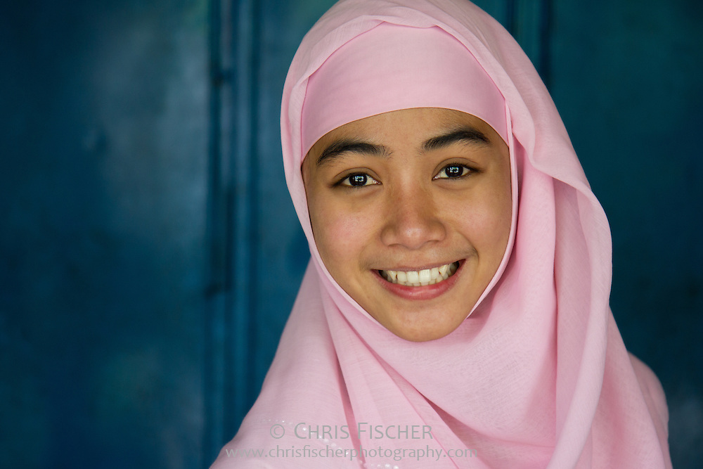 Cheerful young Muslim Indonesian woman wearing pink headscarf (hijab).
