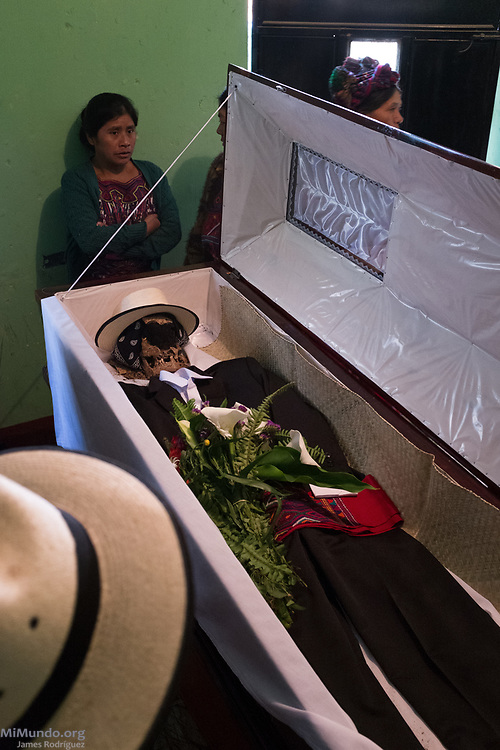 Family members watch as the remains of Tomás Corio Solis are arranged in a coffin. Ixil Mayan residents of Nebaj gather as the human remains of 36 war victims, including Solis de Leon's, are returned to their surviving family members for a proper burial. Most of the victims, exhumed from mass graves in Xe'xuxcap, near Acul, starved in the mountainside while fleeing State-led repression in 1982. Most of the remains, exhumed by members of the Forensic Anthropology Foundation of Guatemala (FAFG) in 2013, were identified using DNA analysis and buried 35 years after their death. Nebaj, Quiché, Guatemala. February 2, 2017.