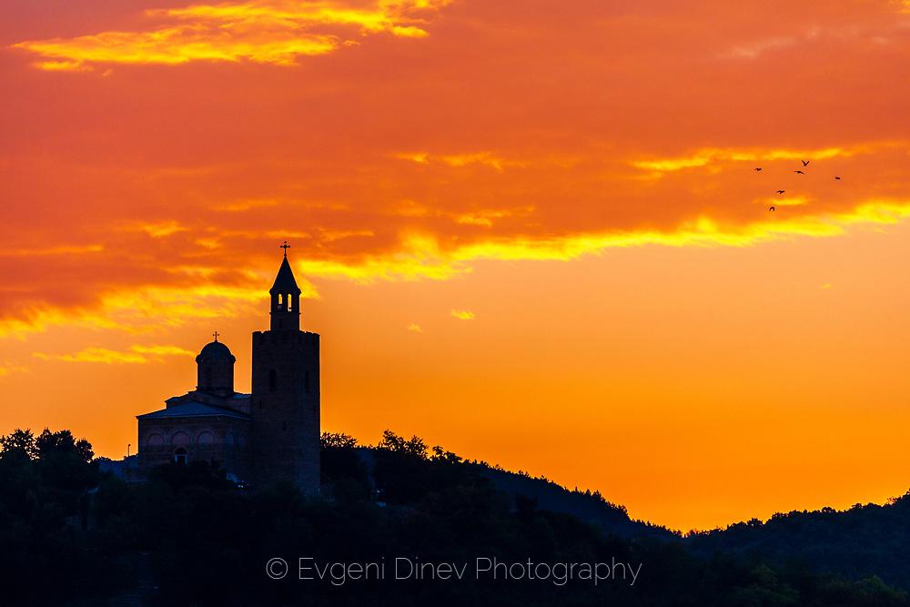 The siluet of church tower on a hill st sunrise