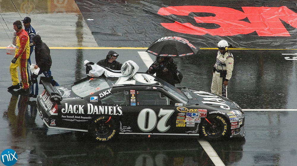 Casey Mear's crew covers his Chevrolet during a rain delay at the Coca-Cola 600 Monday afternoon at Lowe's Motor Speedway. (Photo by James Nix)