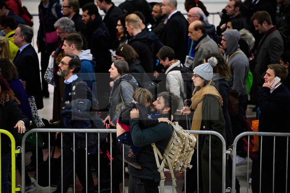 © Licensed to London News Pictures. 14/12/2016. London, UK. A man embraces his child as members of the public queue in the hope of getting a Southern Rail Gatwick Express train at afternoon rush hour at Victoria Station on 14 December 2016. Hundreds of thousands of rail passengers face a second day of a 3 day all-out strike in an escalating dispute over the role of conductors between Southern Rail and the RMT Union. Photo credit: Ben Cawthra/LNP