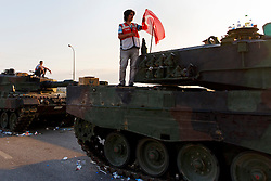 © Licensed to London News Pictures. 17/07/2016. Istanbul, Turkey. Turkish police officers protect army tanks left outside Istanbul's Sabiha Gokcen airport following a failed coup attempt by groups in Turkish military on 15 July 2015. Many tourists whose flights were delayed or cancelled following Friday's coup attempt try to get new flights on Sunday, 17 June 2016. Photo credit: Tolga Akmen/LNP