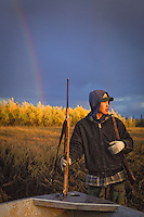 Subsistence hunter, Henry Spein, looks into the late afternoon light with hopes of spotting a moose along the Kuskokwim River near Aniak