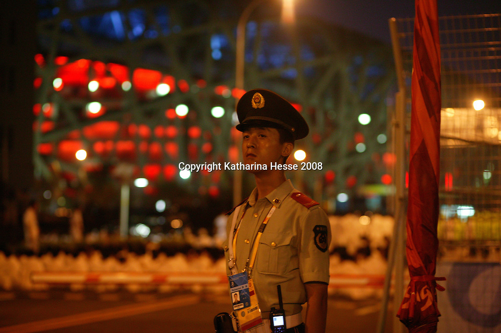 BEIJING, AUGUST 5 :  a soldier stands guard at one of the gates of the National Stadium during dress rehearsals  .