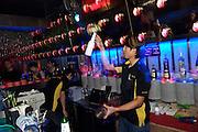Huhai and Qianhai Lake nightlife district. A bar tender showing his juggling tricks.