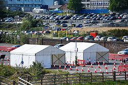 © Licensed to London News Pictures. 26/04/2020. WATFORD, UK. Watford General Hospital (in the background) and a testing centre which opened in the car park on 23 April (shown as two white tents).  Those eligible to use the test centre are hospital staff members or their household who are symptomatic of Covid 19.  To accelerate the testing programme towards a target of 100,000 tests per day by 30 April set by Matt Hancock, Health Secretary, many more testing centre have been set up in the last few days including mobile pop-up test centres. Photo credit: Stephen Chung/LNP
