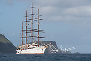 The Sea Cloud, a tall wooden sailing ship is anchored off the coast of Saint Vincent and the Grenadines.