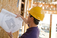 Worker holding blueprint in construction site