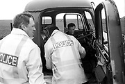 A46 police officers searching a truck. Solsbury Hill, Somerset, UK, 1994.