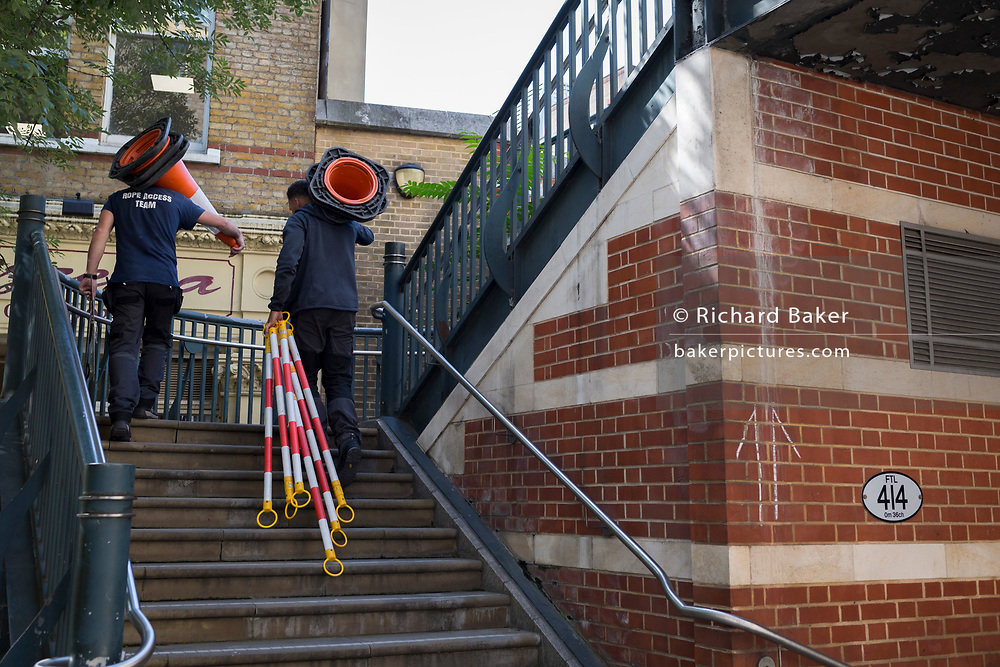 Climbing steps at Blackfriars, workmen carry cones and equipment necessary for overhead work in the City of London, the capital's financial district (aka the Square Mile), on 22nd August 2019, in London, England.