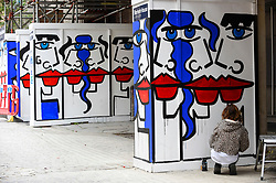 """© Licensed to London News Pictures. 04/08/2020. LONDON, UK.  Artist Anna Laurini works on her new artwork """"Urban Spinxes"""".  Located outside a construction site just off Carnaby Street, the piece is  inspired by Pablo Picasso and Henri Matisse.  The construction company commissioned the artist to design something to cover up what would otherwise be bare wooden hoardings.  Photo credit: Stephen Chung/LNP"""
