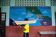 Ban Koh Adang school. Mural painting with the settlement route of the Chao Le people in the Andaman Sea. A student carries a model boat for the annual sea offering ceremony Loy Rua.