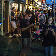 OCCOQUAN, VA - AUG4: People play Pokemon Go in Occoquan, Virginia, August 4th, 2016. This sleepy Virginia town has become a hotspot for Pokemon Go. Throughout the night, kids and young adults play the game on the streets, leaving beer bottles and litter behind. A few residents have complained to city hall and now the city is hiring extra police officers to handle the new masses. (Photo by Evelyn Hockstein/For The Washington Post)