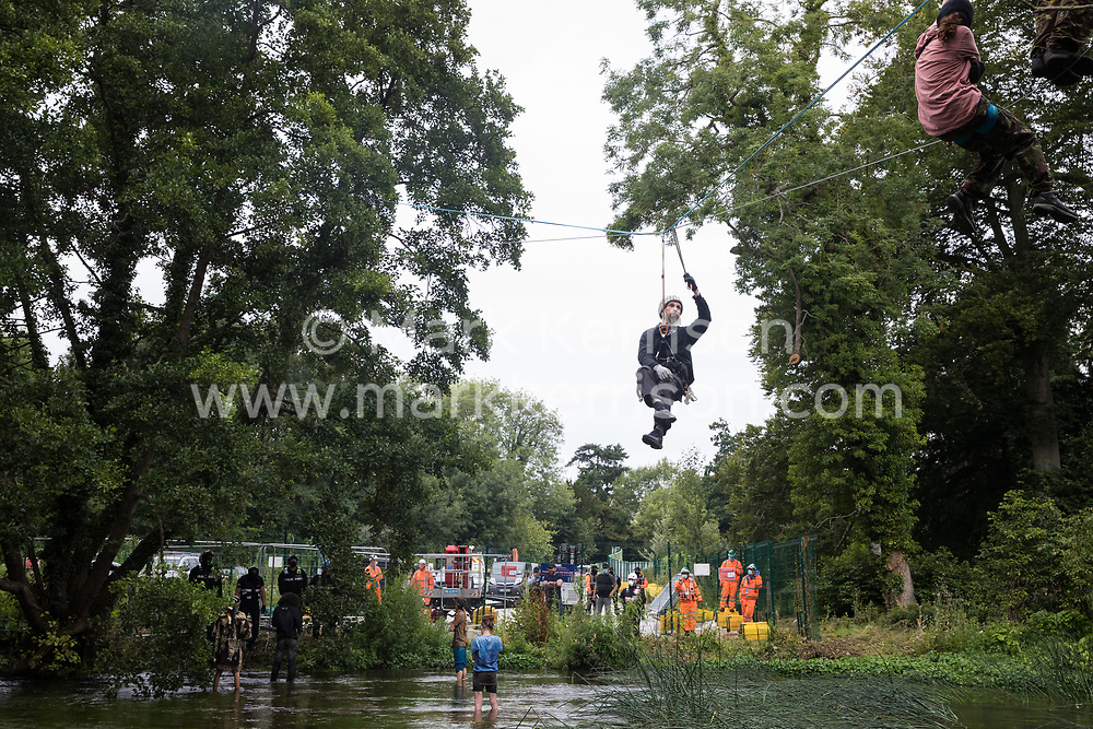 Denham, UK. 24 July, 2020. Larch and other environmental activists from HS2 Rebellion use a line above the shallow river Colne attached to an ancient alder tree to try to protect it from destruction in connection with works for the HS2 high-speed rail link in Denham Country Park. A large policing operation involving the Metropolitan Police, Thames Valley Police, City of London Police and Hampshire Police as well as the National Eviction Team was put in place to enable HS2 to remove the tree. 2020 is the Year of the Tree.