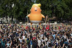 © Licensed to London News Pictures. 13/07/2018. London, UK. A giant inflatable balloon depicting President Trumpas a baby in a nappy is flown over Parliament Square. President Trump is on the second day of a four day visit to the UK. Photo credit: Peter Macdiarmid/LNP