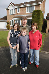 Family group standing outside their house,