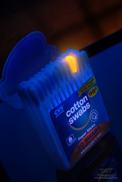 A container full of cotton swabs, with one that glows a bright orange.Black light