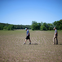 Thomas Wells | BUY at PHOTOS.DJOURNAL.COM<br /> Matthew Barber, left, and his brother, Jon Paul, check a field to see how much spor planting they will have to do in order to fill in for lost seds due to last weeks heavy rain.