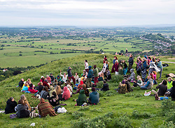 © Licensed to London News Pictures; 20/06/2020; Glastonbury, Somerset, UK. People gather on Glastonbury Tor for sunset on the Summer Solstice weekend on the longest day of the year today at midsummer. This year due to the coronavirus Covid-19 pandemic and concerns over social distancing at gatherings of people, Stonehenge and Avebury where thousands of people usually gather to celebrate the summer solstice are closed to the public, with the solstice live streamed from Stonehenge. Glastonbury authorities had also asked people to refrain from coming to Glastonbury for the solstice but hundreds came with many staying the night on the Tor. Glastonbury Tor is a hill outside Glastonbury town, topped by the roofless St Michael's Tower, a Grade I listed building which is what remains of the Church of St Michael built in the 14th century. The entire site is managed by the National Trust and has been designated a scheduled monument. Photo credit: Simon Chapman/LNP.