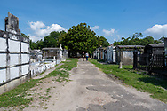 New Orleans, LA, USA -- May 26, 2019.  Wide angle landscape photo of  St Louis Cemetery #3; couple in the distance walks along a path.