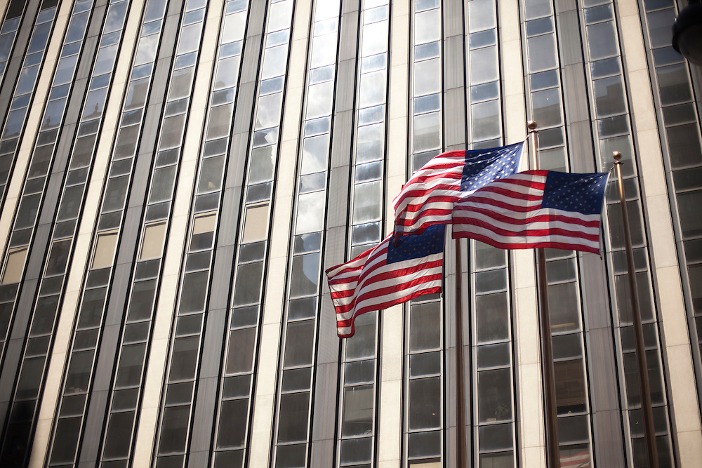 Three American flags in front of one of the skyscrapers of Manhattan.