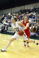 29 January 2011: Olivia Lett defended by Cailee Corcoran during an NCAA Womens basketball game between the Carthage Reds and the Illinois Wesleyan Titans at Shirk Center in Bloomington Illinois.