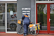 Nederland, Millingen, 2-5-2017Een postbode maakt zijn ronde op de fiets.Foto: Flip Franssen