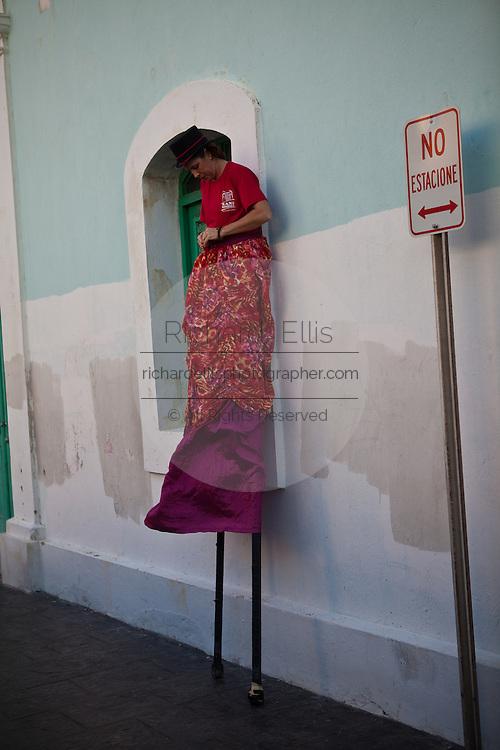 A stilt walker rests after parading through the streets of Old San Juan during the Festival of San Sebastian in San Juan, Puerto Rico.