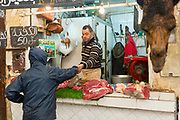 FEZ, MOROCCO - 05th MARCH 2016 - Customer buying camel meat from a  butchers stall in the old Fez Medina, Middle Atlas Mountains, Morocco.