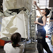 Two of the technical crew discuss the shaping of the legs.  Aurora is a giant polar bear puppet, the size of a London double decker bus. The bear is the brain child of Greenpeace UK and it will be the center piece in the Greenpeace campaign Save the Arctic  global day of action in London Sept 15th. Aurora is designed by Christopher Kelly in collaboration with props designer Simon Costin and made by Factory Settings in East London.