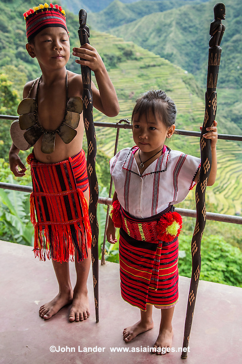 "Ifugao Tribe Indigenous Children posing in native costume in front of Batad Rice Terraces - a UNESCO world heritage site. Ifugao means ""earth people"" or ""from the hills"" who inhabit the mountains of the Philippines Cordilleras. Igorot is the collective name of these indigenous tribes who inhabit these regions"