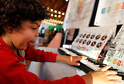 Levi Choi, 5, of Irondequoit, plays an electric keyboard at the Democrat and Chronicle Digital Jazz Club on Saturday, June 21, 2014.