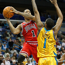 February 12, 2011; New Orleans, LA, USA; Chicago Bulls point guard Derrick Rose (1) shoots over New Orleans Hornets small forward Trevor Ariza (1) during the fourth quarter at the New Orleans Arena.  The Bulls defeated the Hornets 97-88. Mandatory Credit: Derick E. Hingle