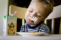 JEROME A. POLLOS/Press..Gavin Scheel, 2, attempts to make due with using a fork with his mouth Friday to eat his lunch.