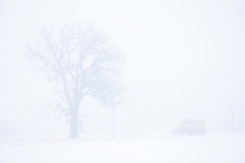 Snowplow on a rural road, foggy winter day