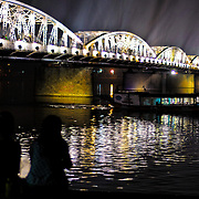 A couple sits on the waterfront of the Perfume River in Hue, Vietnam, at night, silhoutted against the brigh illumination of the bridge.