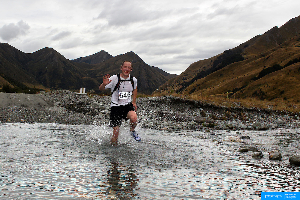 Runner Paul Bibby crosses Moke Creek on the Ben Lomond High Country Station during the Pure South Shotover Moonlight Mountain Marathon and trail runs. Moke Lake, Queenstown, New Zealand. 4th February 2012. Photo Tim Clayton