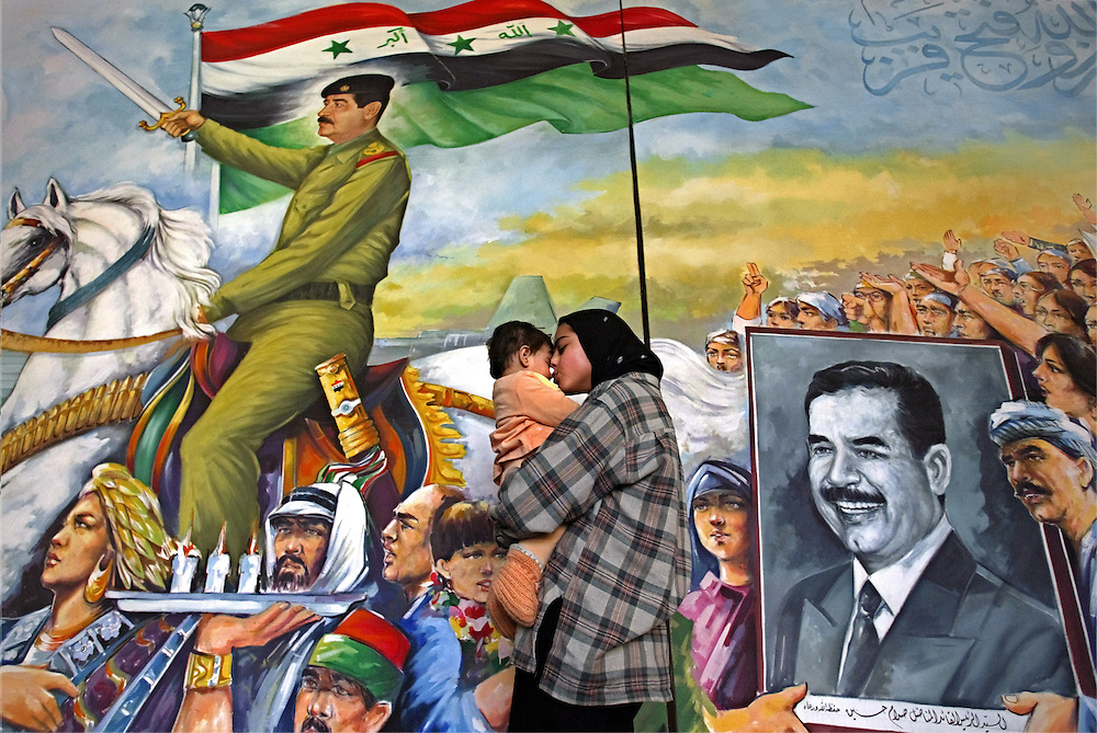 Iraqi woman holds her child standing at the poster with Saddam Hussein portraits in Iraqi Modern Art Center in Baghdad, 12 February 2003. The exhibition of this and others 30 paintings by the artist Shakir Halit are exposed on the exhibition `The presents to Saddam Hussein`.